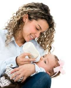 Mother feeding her baby from a bottle - isolated over white