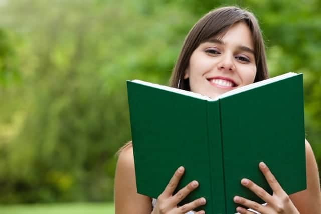 smiley young woman holding a book outdoors
